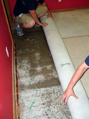 Julington Creek water damaged carpet being removed by two men.